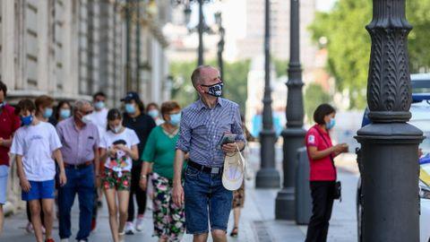 Viandantes con mascarillas en las inmediaciones del Palacio Real, en Madrid