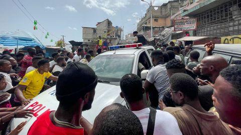 Decenas de personas rodean un coche policial en el que permanecían custodiados dos extranjeros capturados por un grupo de ciudadanos como sospechosos del crimen
