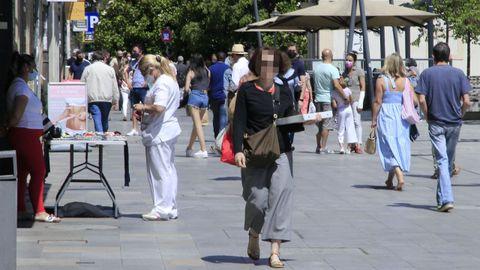 Una mujer paseando sin mascarilla frente a la Diputación de Lugo