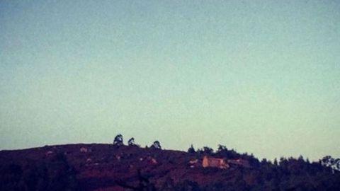 El monte Chamorro al anochecer, con la ermita de Nosa Señora do Nordés en la lejanía...