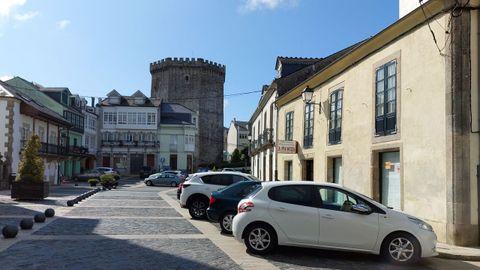 Coches aparcados en la plaza de Santa María, con la torre de los Andrade al fondo
