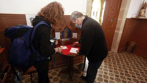 Andrés Garcìa le sella la credencial a una peregrina que empieza el Camino en Sarria