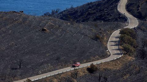 Un automóvil circula por la carretera que discurre por la zona del incendio que, desde este viernes afectó al parque natural de Cap de Creus y que fue estabilizado este domingo.