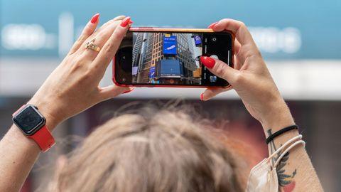 Una mujer sacando una fotografía durante el despegue en Times Square, Nueva York