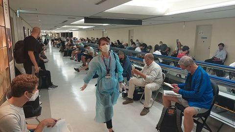 Una voluntaria, con una prenda de protección, trata de organizar la llegada de una de las delegaciones olímpicas a Narita