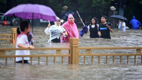 Personas caminando sobre la carretera inundada en la ciudad china de Zhengzhou