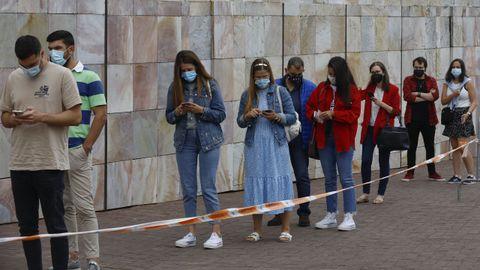 Los primeros veinteañeros citados el jueves en Santiago esperan su turno para la vacuna