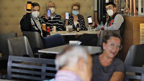Clientes en la cafetería Rosalía muestran sus certificados de vacunación en el móvil