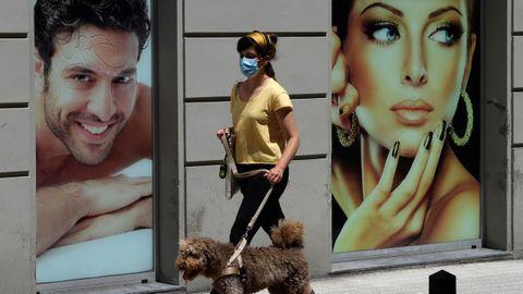 Una chica con su perro pasea con mascarilla por una céntrica calle de Gijón