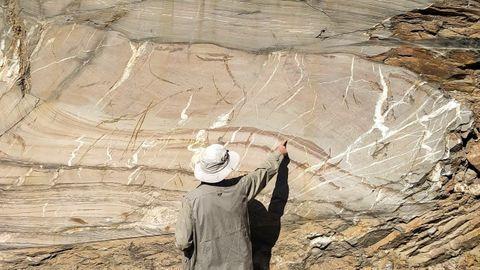 Un investigador observa un pliegue geológico en una cantera de la localidad de Vilarbacú, en el municipio de Quiroga