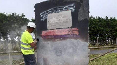 Un trabajador restaura el monolito de la memoria democrática de Arnao, en Castropol