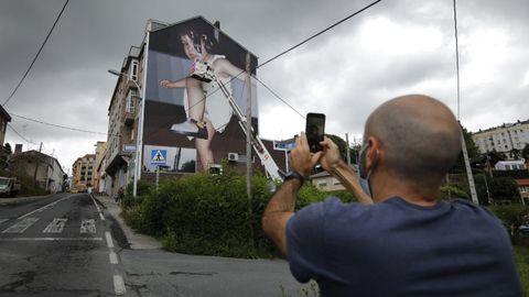 Slim Safont desde la grúa dio los últimos retoques a su mural en la rúa Amil.