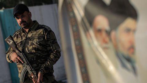Un guarda paramilitar chií hace guardia frente a un hospital en Sadr City