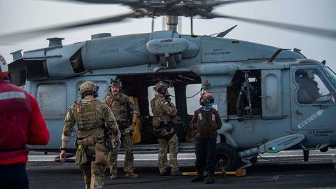 Marineros estadounidenses de la Unidad Móvil de Desactivación de Artefactos Explosivos a bordo de un helicóptero en la cubierta de vuelo del portaaviones USS Ronald Reagan (CVN 76) se preparan tras recibir una llamada de auxilio del Mercer Street