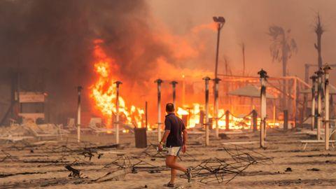 Un hombre camina frente al fuego en una playa de Catania, Sicilia, el pasado 30 de julio cuando dieron comienzo los graves incendios