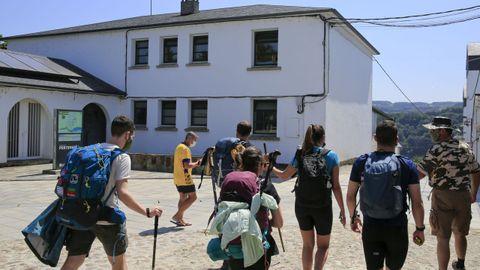 Peregrinos pasando ante el albergue municipal de Portomarín, utilizado para casos de aislamiento