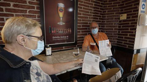En imagen de archivo, dos clientes de un establecimiento hostelero de A Mariña mostrando el certificado covid para acceder al interior