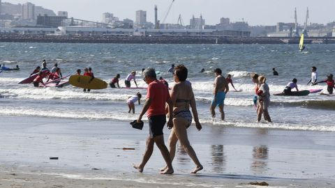 Gente paseando por la orilla de la zona de surf, donde imparten clase las escuelas