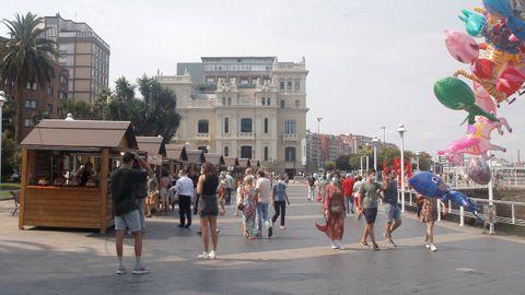Personas paseando en la trigésima Fiesta de la Sidra Natural de Gijón ha comenzado este sábado con 22 participantes en un mercadillo de productos artesanos derivados de la manzana y se desarrollará hasta el próximo 29 de agosto