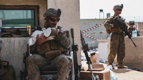 El sargento  Isaiah Campbell sostiene al bebé tras recogerlo del muro del aeropuerto de Kabul.