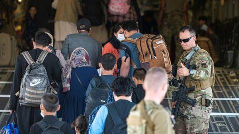 Miembros de las fuerzas militares escoltan a un grupo de ciudadanos antes de embarcar en un avión en el aeropuerto de la ciudad de Kabul