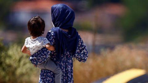 Una evacuada afgana camina con su hijo en el centro de detención administrado por la Cruz Roja Italiana en Avezzano.