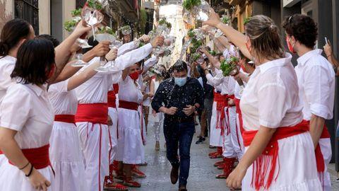 Jóvenes de la localidad barcelonesa de Arenys de Mar bendicen con agua perfumada al presidente Pere Aragonès durante una fiesta el pasado 16 de agosto