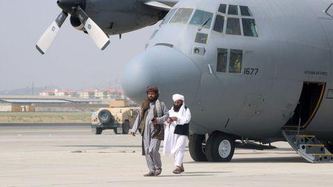 Los talibanes pasean frente a un avión militar tras la retirada de las tropas estadounidenses del aeropuerto de Kabul