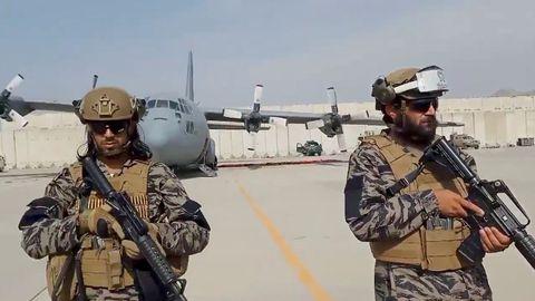 Miembros de la unidad militar montan guardia mientras el portavoz talibán pronuncia su discurso en el aeropuerto de Kabul