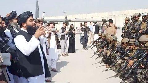 Miembros de la unidad militar montando guardia mientras el portavoz talibán pronuncia su discurso