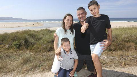 Alberto, con sus padres y su hermano menor, este martes en la playa de Traba (Laxe)