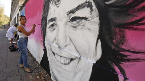 Yasmina Torres da los últimos retoques a su mural de Paula García Couce, en el muro del Sánchez Aguilera