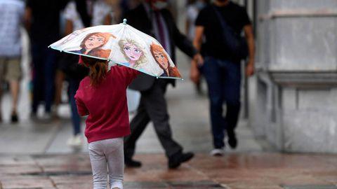 Una niña se protege esta tarde de la lluvia en una céntrica calle de Oviedo