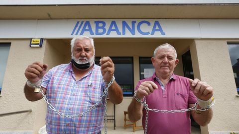 Roberto Vázquez, a la izquierda, junto al vecino con el que se ha encadenado a la oficina