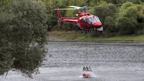 Un helicóptero carga en el río Sil para llevar agua al incendio de Ribas de Sil.