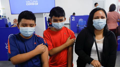 Dos menores, junto a su madre, después de recibir su vacunas contra el covid-19 en El Salvador