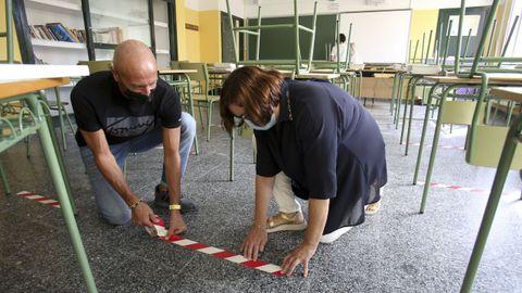 Personal del IES Canido marca la ubicación de cada pupitre para mantener la distancia de seguridad entre alumnos, que pasa de 1,5 a 1,2 metros