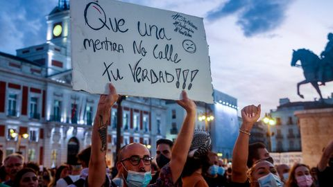 Un manifestante sostiene una pancarta durante una concentración en la Puerta del Sol contra las agresiones a las personas LGTBI