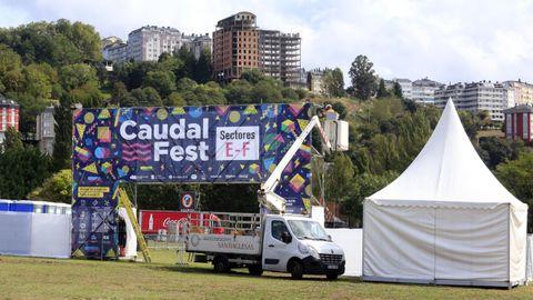 Un operario, colocando el cartel del Caudal Fest.