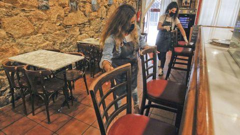 Vanessa Martínez colocando sillas en la barra del café Sevilla