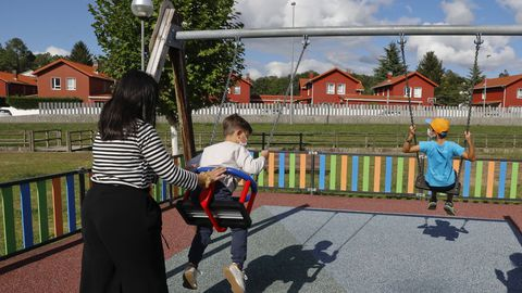 Niños jugando en el parque infantil de la urbanización Agro Do Muíño, este sábado