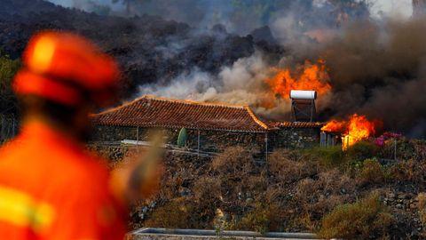 Un miembro de Protección Civil observa un casa que arde por el efecto de la lava