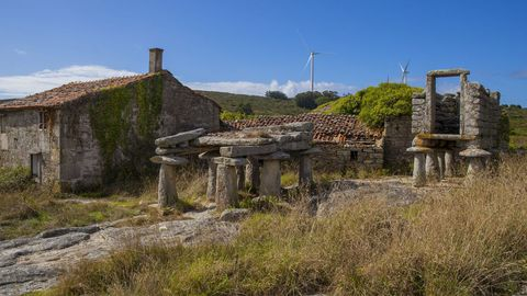 Antiguos hórreos y casas de piedra sobreviven, como buenamente pueden, en la aldea cormelana de Candelago
