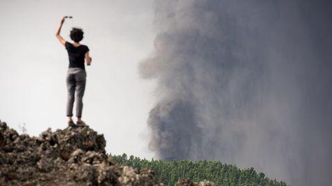 Una mujer observa el volcán