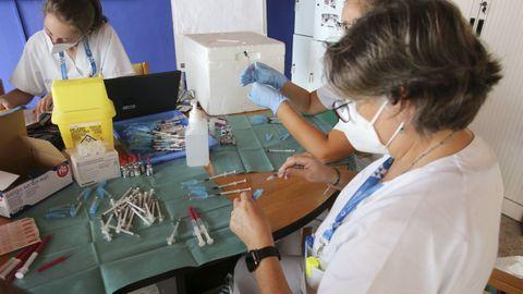 Varias sanitarias preparan dosis de las vacunas contra el covid en el centro de mayores de Laraxe, en Fene