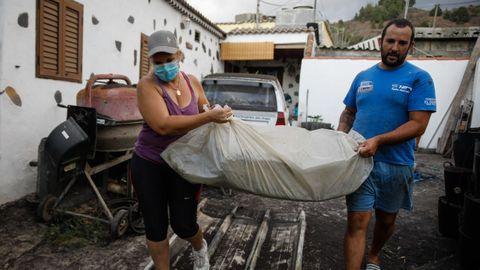 Un hombre y una mujer sacan sus pertenencias en Tajuya, una de los barrios desalojados el viernes tras el repunte de la actividad volcánica