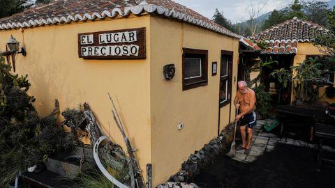 Un hombre barre la ceniza esparcida en las inmediaciones de su vivienda, en Tacande de Arriba
