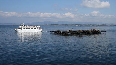 Un barco turístico junto a una batea en O Grove.