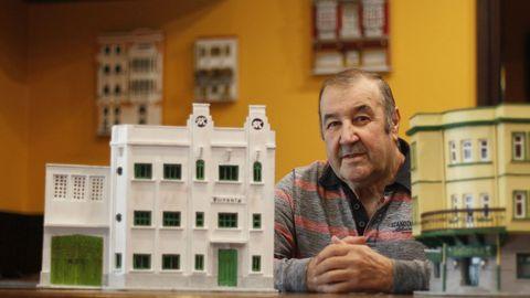 Carlos Macías, fotografiado entre su maqueta de la fábrica Hispania, la más reciente, y otra del edificio del bar Galerna, donde exhibe sus creaciones