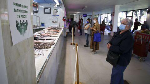 Vecinas de As Pontes aguardando su turno en un puesto del mercado municipal.